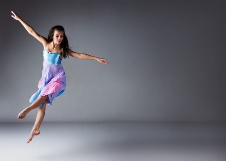 Beautiful female modern jazz contemporary style dancer on a grey background. Dancer is barefoot and wearing a blue and purple dress.