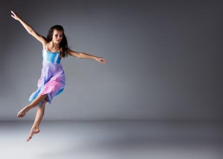 Belle femme moderne jazz danseuse de style contemporain sur un fond gris. Dancer est pieds nus et vêtue d'une robe bleu et violet. Banque d'images - 23548486