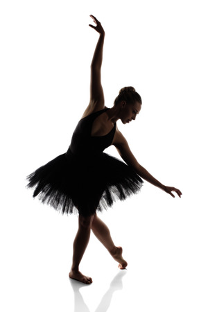 contemporary dance: Beautiful young female classical ballet dancer in silhouette wearing a black leotard and tutu isolated on a white studio background
