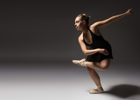 danza contemporanea: Hembra joven hermosa bailarina de ballet clásico en zapatillas de punta usando un leotardo negro y falda en un estudio de fondo gris neutro