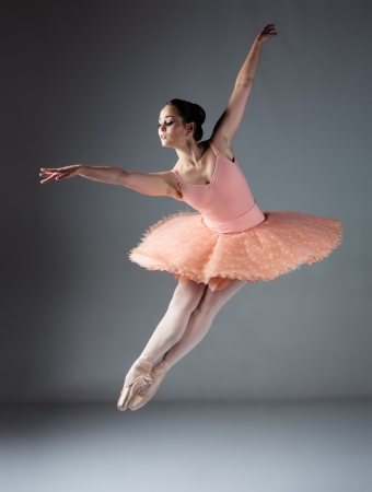 ballet dancing: Beautiful female ballet dancer on a grey background. Ballerina is wearing an orange tutu, pink stockings and pointe shoes.