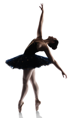 Silhouette of a beautiful female ballet dancer isolated on a white background. Ballerina is wearing a royal blue tutu and pointe shoes.