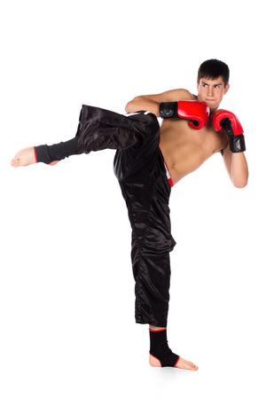 Jonge knappe mannelijke blanke kickbokser dragen van rode bokshandschoenen en kickboksen gear geïsoleerd op een witte achtergrond Stockfoto