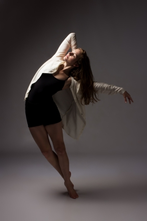 contemporary: Beautiful slim young female modern jazz contemporary style ballet dancer wearing a black leotard and white shirt on a neutral grey studio background