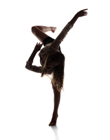 performing: Beautiful slim young female modern jazz contemporary style ballet dancer in silhouette wearing a black leotard and white shirt isolated on a white studio background
