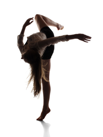 Beautiful slim young female modern jazz contemporary style ballet dancer in silhouette wearing a black leotard and white shirt isolated on a white studio background photo