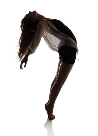 Mooie slanke jonge vrouw moderne jazz eigentijdse stijl balletdanser in silhouet gekleed in een zwarte maillot en een wit overhemd geà ¯ soleerd op een witte achtergrond studio