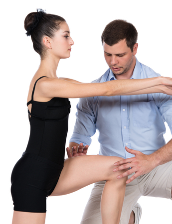 Adult male physiotherapist is assisting a female patient in rehabilitation exercises.