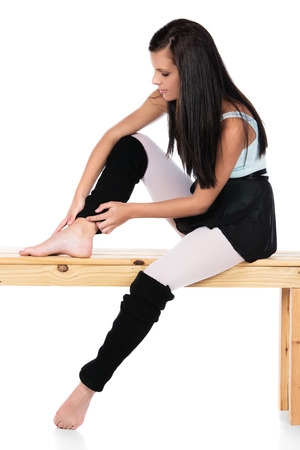 leg warmers: Beautiful female modern jazz contemporary style dancer isolated on a white background. Dancer is wearing a blue leotard, black skirt and leg warmers and is holding her injured ankle. Stock Photo