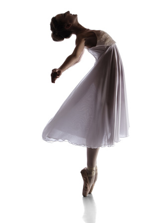 Silhouette of a beautiful female ballet dancer isolated on a white background. Ballerina is wearing a white dress with feathers and pointe shoes. photo