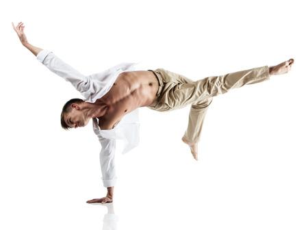 Volwassen Kaukasische mannelijke danser draagt een wit shirt en beige broek. Beeld is geïsoleerd op een witte achtergrond.