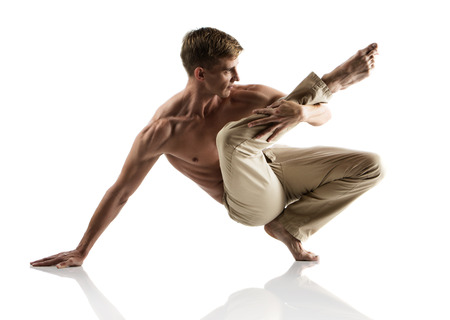 Adult caucasian male dancer wearing beige pants. Image is isolated on a white background.