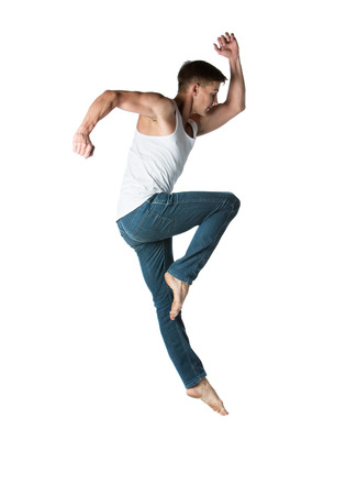 Adult male dancer wearing a white shirt and jeans. Image is isolated on a white background.