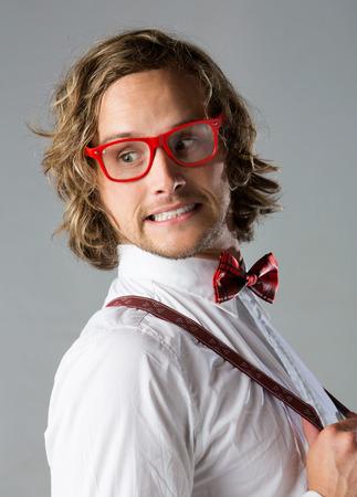 Portret van een knappe blanke man met een witte dichtgeknoopt hemd, rood geruit vlinderdas, bretels en funky bril. Stockfoto