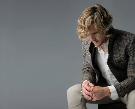 chinos: Portrait of a handsome caucasian man wearing a white buttoned shirt, brown checkered retro jacket and beige chinos. The man is sitting.