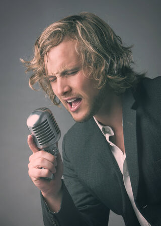Portrait of a handsome caucasian male singer wearing a white buttoned shirt and a grey jacket. The man is singing into a silver performance microphone.