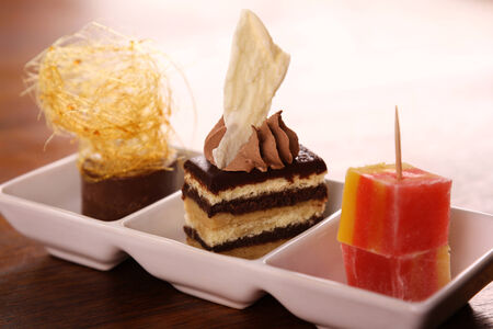 three layered: Three beautiful delicious gourmet desserts on a white plate. Chocolate layered cake, fudge, mousse and turkish delights.