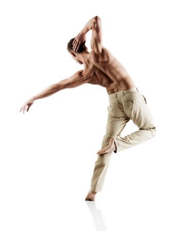 成人白人男性ダンサーはベージュのズボンを着用します。イメージは、白い背景に分離されます。