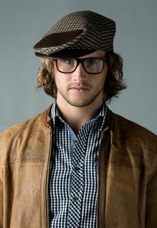 Portret van een knappe blanke man met een leren jas blauw geblokte knoopoverhemd baret en retro bril.