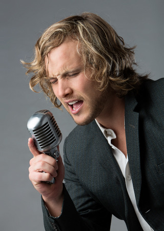 Portrait of a handsome caucasian male singer wearing a white buttoned shirt and a grey jacket. The man is singing into a silver performance microphone. photo