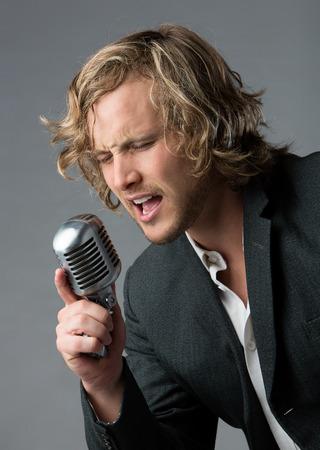 Portret van een knappe blanke mannelijke zanger draagt een wit dichtgeknoopt overhemd en een grijze jas. De man zingen in een zilveren prestatie microfoon.