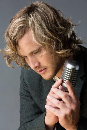 Portret van een knappe blanke mannelijke zanger die een witte dichtgeknoopt overhemd en een grijze jas. De man is poseren met een zilveren prestatie microfoon.