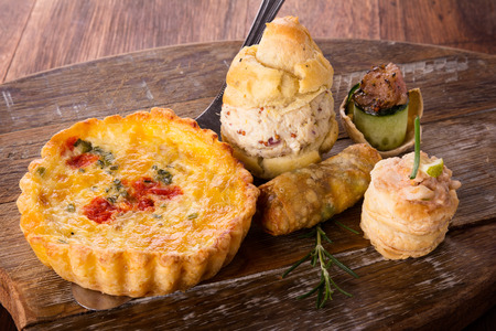 A variety of delicious savory pastries and bites served on a wooden board. The selection includes quiches, spring rolls, scones with chicken and seafood. photo