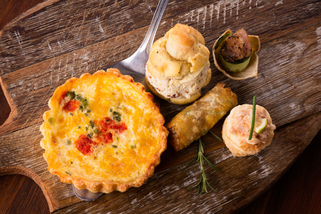 Een verscheidenheid aan heerlijke hartige broodjes en hapjes geserveerd op een houten plank. De selectie omvat quiches, loempia's, scones met kip en vis.
