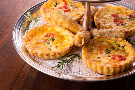 A variety of delicious savory pastries and bites served on a silver cake stand. The selection includes quiches and spring rolls. photo
