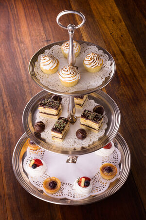 A selection of delicious desserts arranged and served on a silver cake stand in an english high tea style.