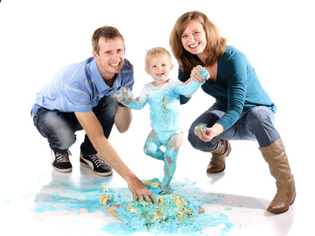Caucasian family with mom dad and baby boy. A one year old baby boy smashing a blue iced birthday cake on a wooden board. Image is isolated on a white background. photo