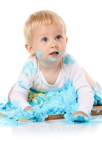 smashing: A one year old baby boy smashing a blue iced birthday cake on a wooden board. Image is isolated on a white background.