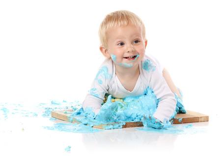 Een een jaar oude baby jongen smashing een blauwe iced verjaardagstaart op een houten plank. Beeld is geïsoleerd op een witte achtergrond.