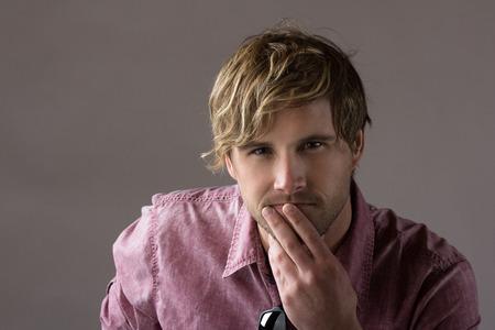 Portret van een knappe blonde blanke man met een bleke paarse knop shirt met een zonnebril.