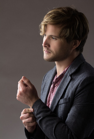 Portrait of a handsome blonde caucasian man wearing a pale purple button shirt with dark grey formal suit jacket. Stock Photo