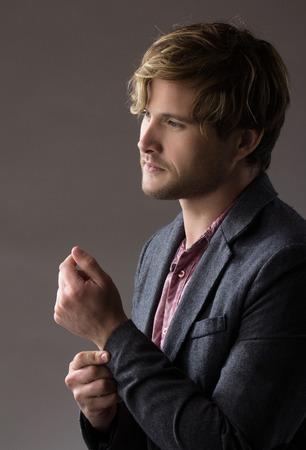 Portret van een knappe blonde blanke man met een bleke paarse knop shirt met donkergrijze formeel jasje.