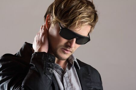 Portrait of a handsome blonde caucasian man wearing a faded blue button shirt, black jacket with leather and sunglasses.