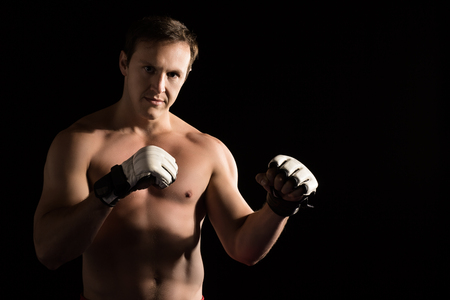 artes marciales mixtas: Portrait of a handsome caucasian male mixed martial arts fighter. The guy is wearing white mma gloves. Foto de archivo