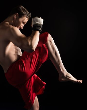 red shorts: Portrait of a handsome caucasian male mixed martial arts fighter. The guy is wearing white mma gloves and red shorts.
