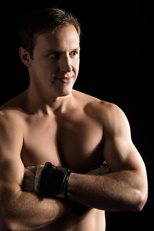 mixed martial arts: Portrait of a handsome caucasian male mixed martial arts fighter. The guy is wearing white mma gloves. Stock Photo