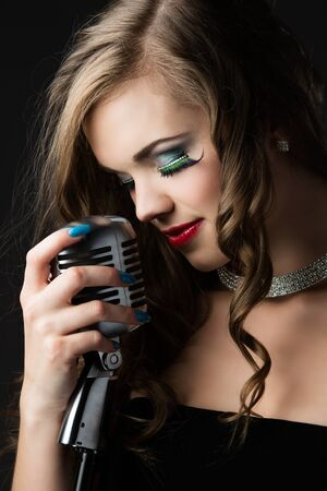 choker: Beautiful caucasian female singer. The girl is holding a retro performance microphone and wearing a black evening dress with a diamond choker necklace and glamor make-up.