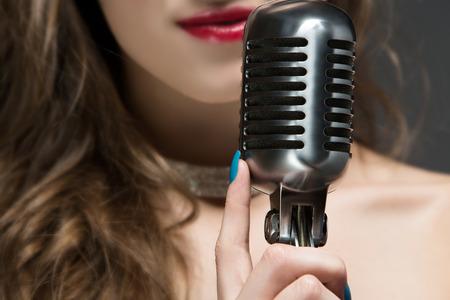 Mooie blanke zangeres. Het meisje houdt een retro prestaties microfoon en het dragen van een zwarte avondjurk met een diamant choker ketting en glamour make-up. Stockfoto