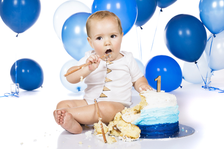 A one year old baby boy smashing a blue iced birthday cake on a silver board with lots of blue helium balloons in the background.