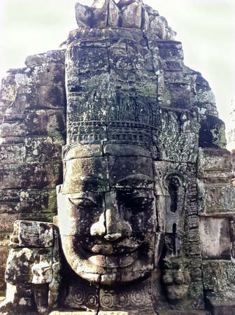 """Sculpture of the smiling stone faces on upper terrace of """"faces tower"""", One from 4 in each tower of the 216 gigantic faces on the temple's name """"Prasat Bayon"""", Khmer architecture style."""