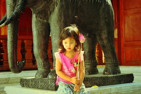 Pretty girl sit near elephant model