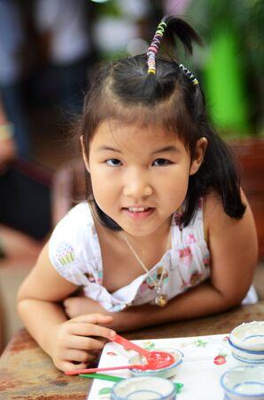 A closeup portrait of  pretty little asian girl smile after eat dessert
