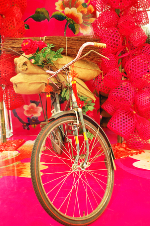 One bicycycle in red background with many little red round bamboo basket. Stock Photo