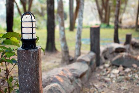 Black and white lamp on concrete pillar in garden alone
