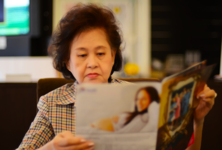 Portrait of asian senior woman reading newspaper