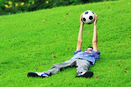 lay down: portrait of Asian boy lay down on grass and hold football in hand over his body